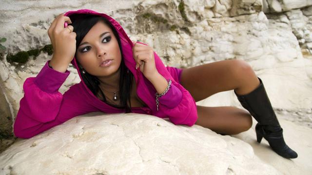 азиатка в капюшоне лежит на камне