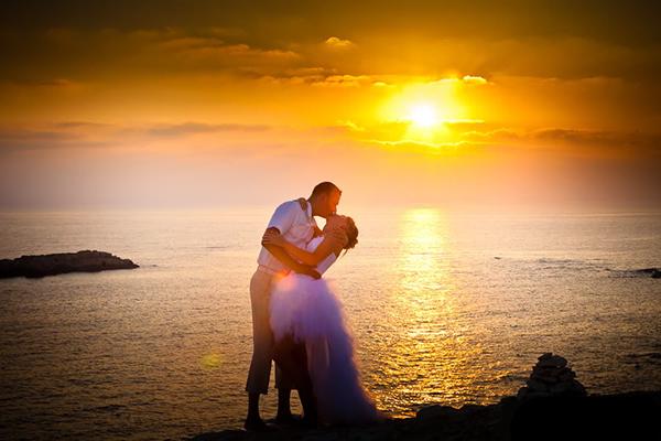 целующиеся на берегу моря жених с невестой